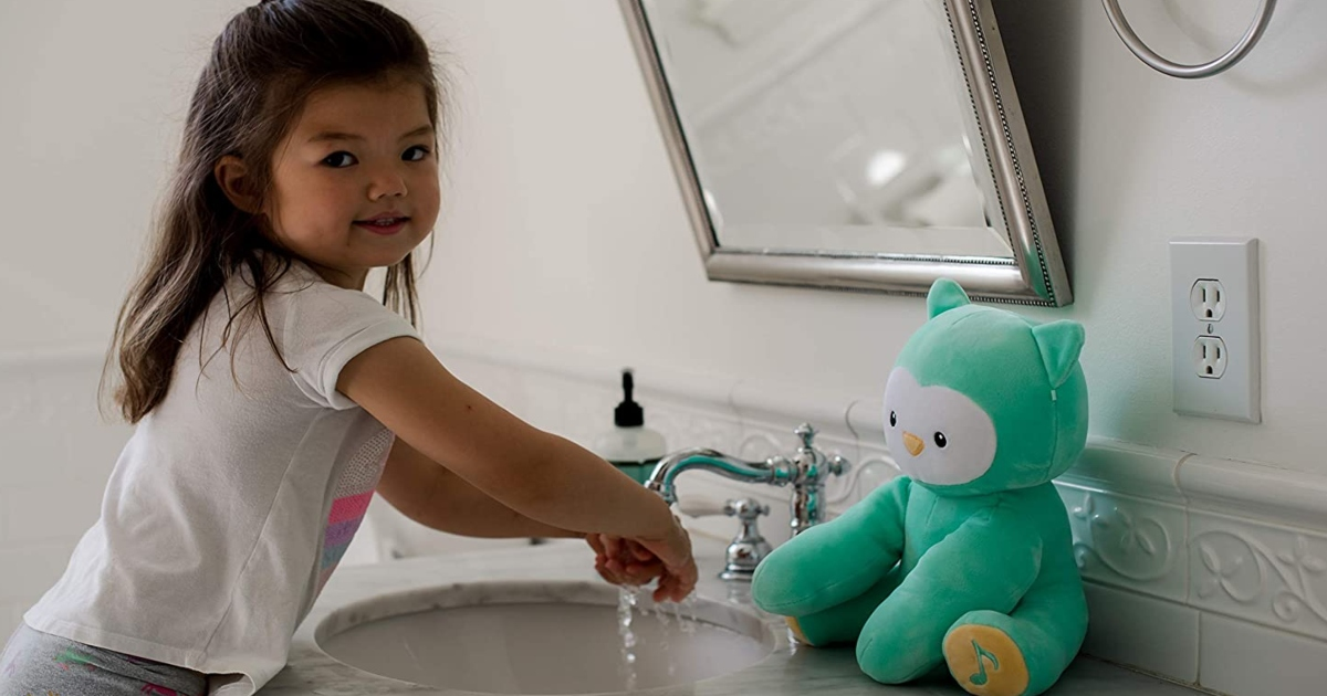 hand washing owl plush near the sink while a young girl is washing her hands