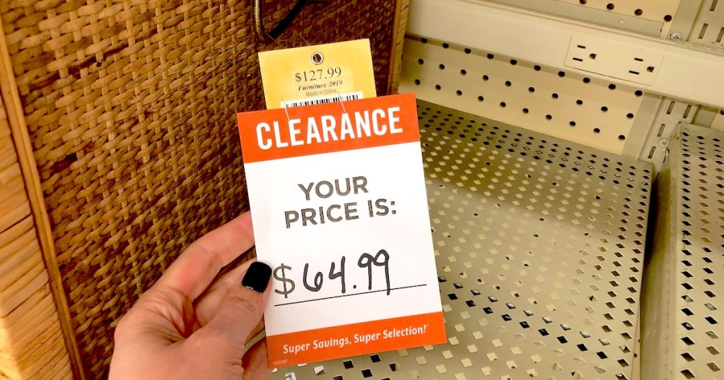 hand holding red and white clearance sticker with price tag on store shelf