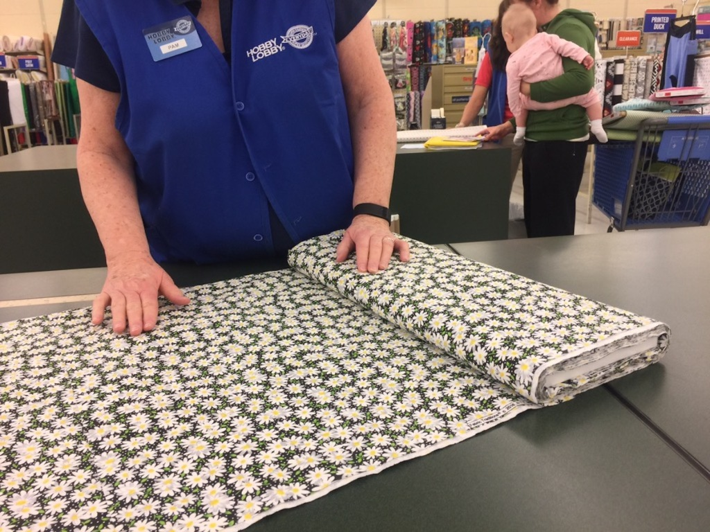 woman rolling out floral fabric on hobby lobby countertop