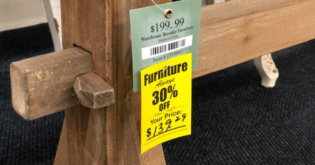 wood table with hobby lobby sale schedule sign on front