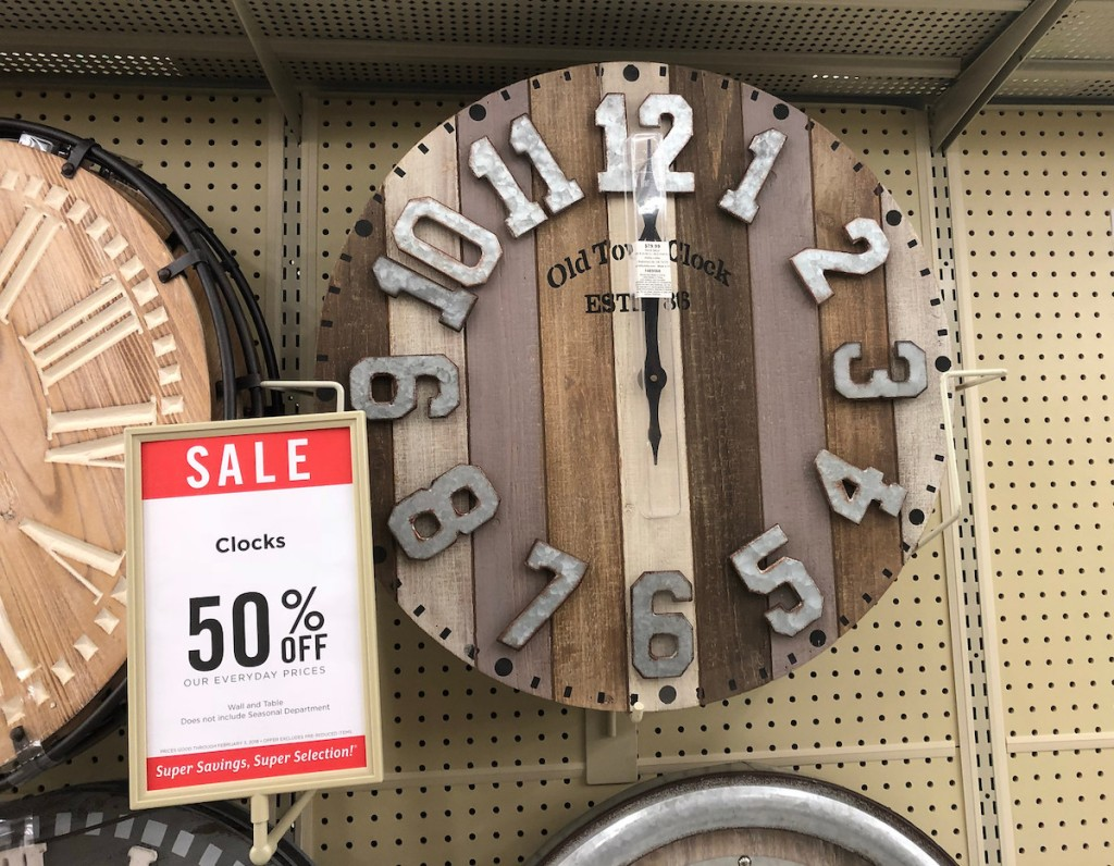 wall clocks hanging on store shelf with hobby lobby sale schedule sign