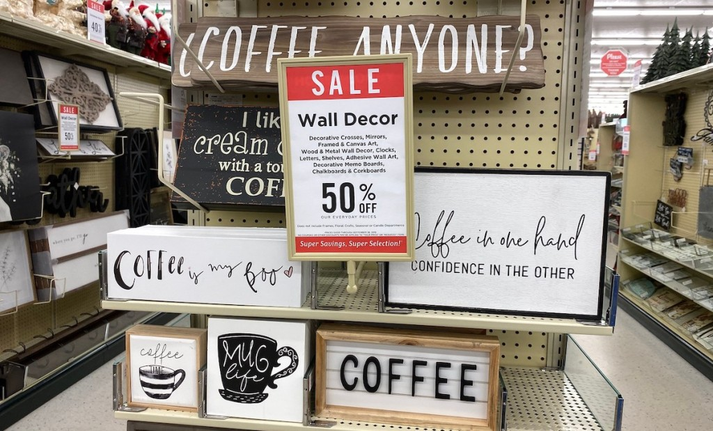 coffee themed wood wall decor hanging on hobby lobby store shelf with sale schedule sign