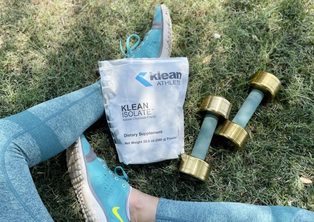 klean athlete protein powder in grass outside