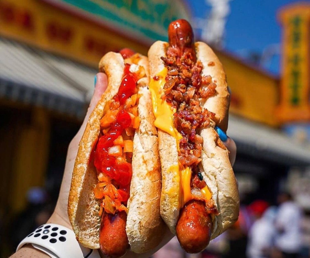 holding 2 hot dogs