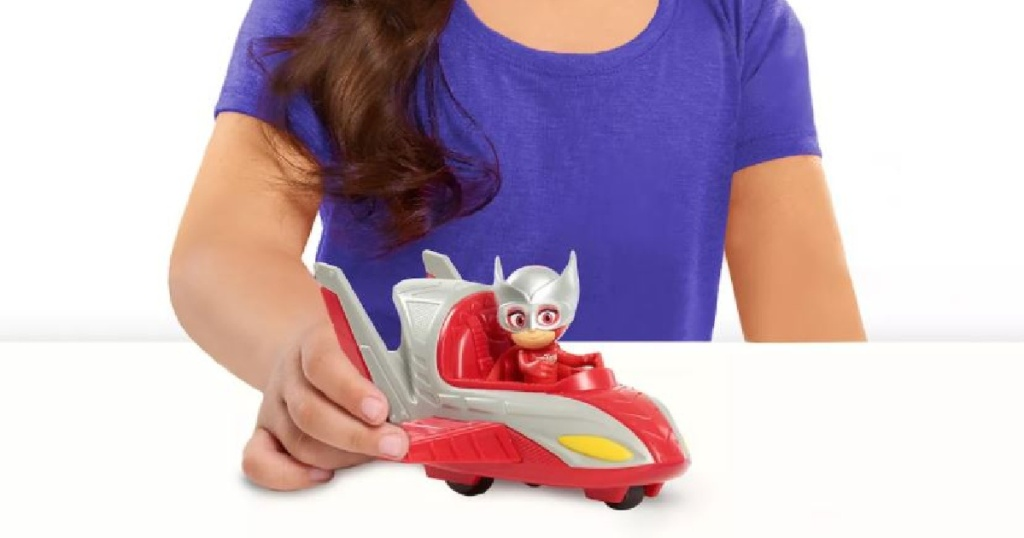 little kid playing with red toy plane/car