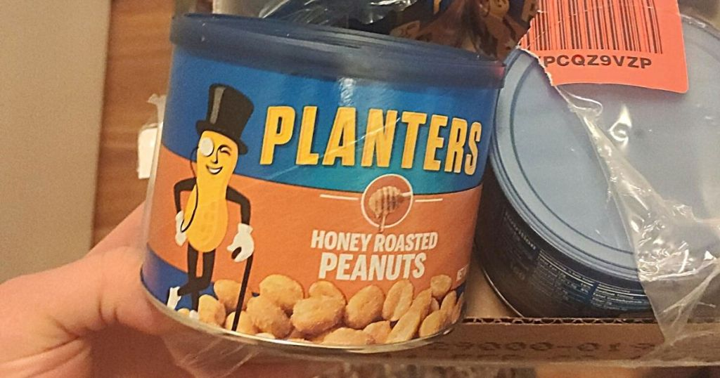 hand taking Planters peanuts from package