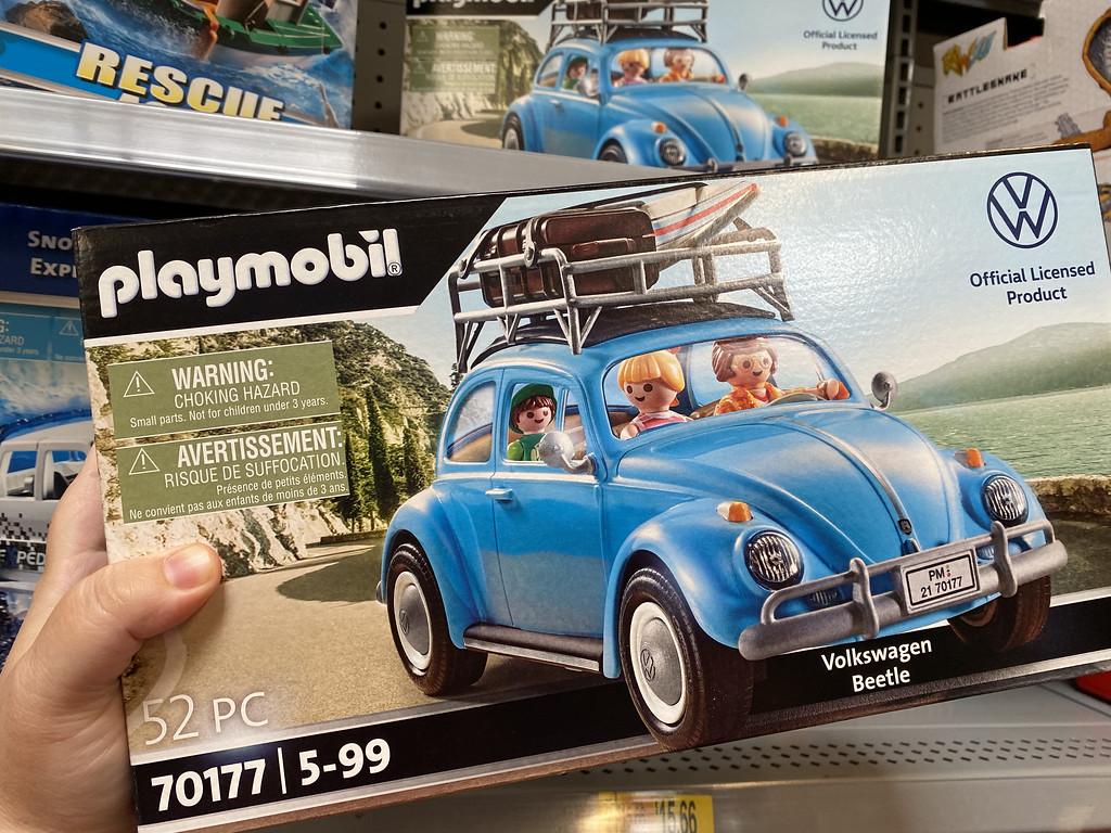 hand holding a playmobil vw bug in box at store