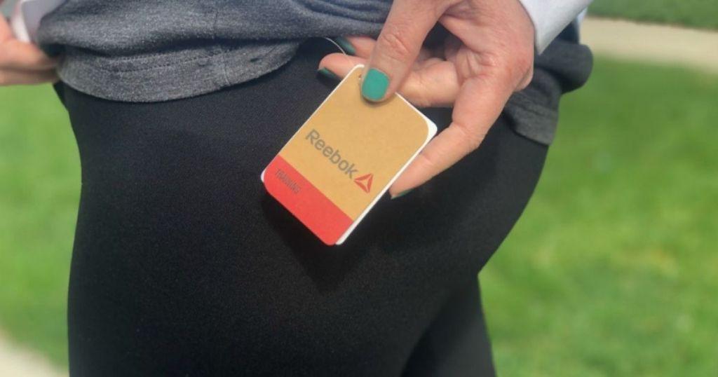 woman holding Reebok tag on black leggings