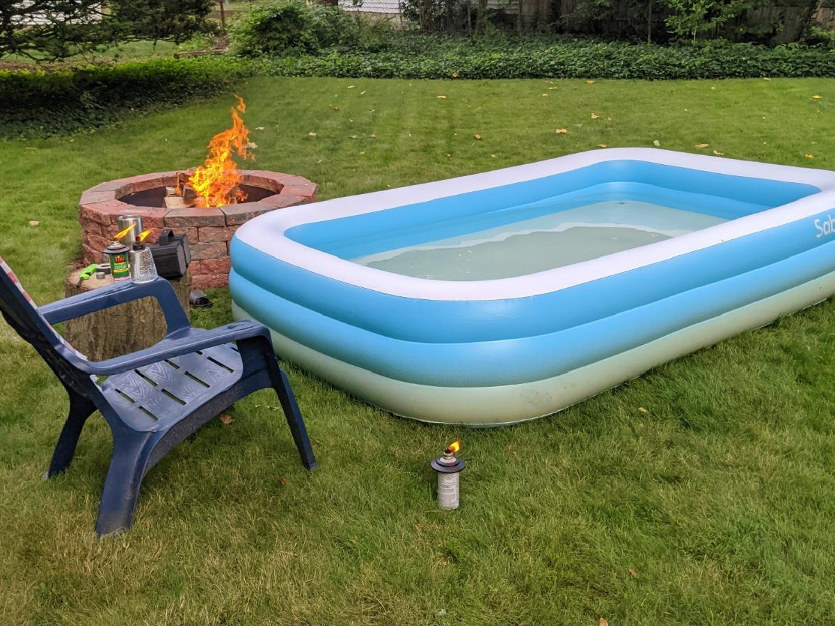 inflatable pool next to a fire pit and plastic chair