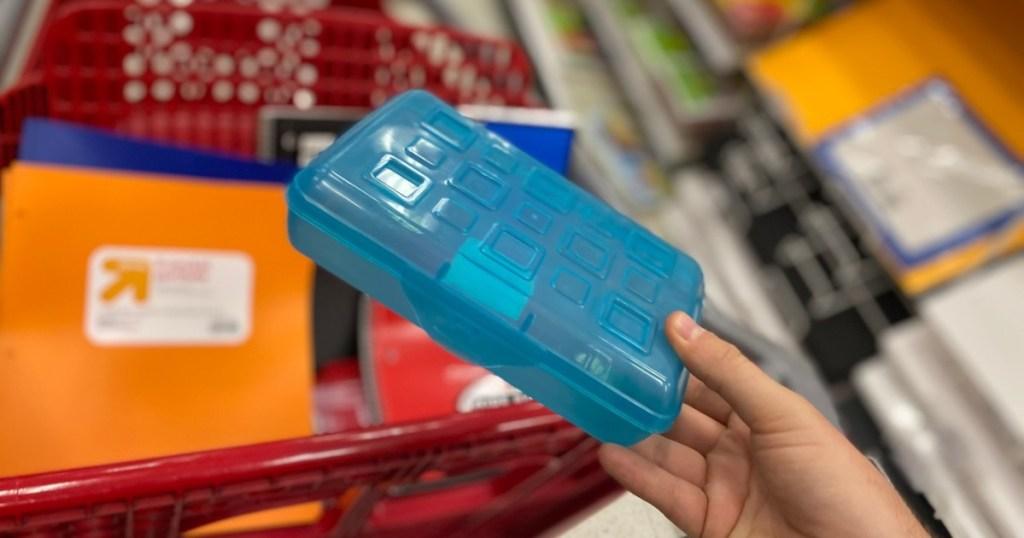 holding a blue pencil box