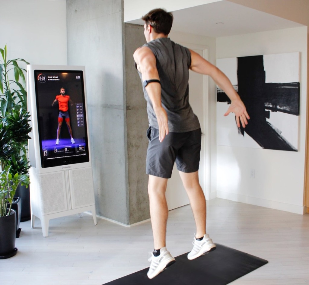 man jumping in front of workout mirror