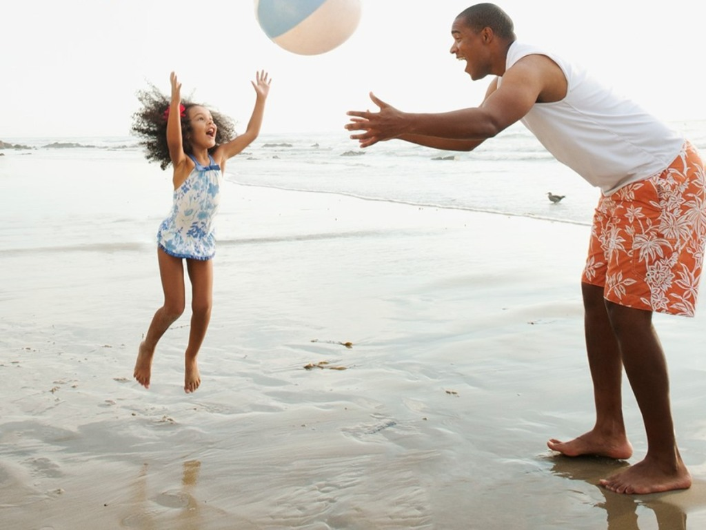 father throwing a beach ball to daughter