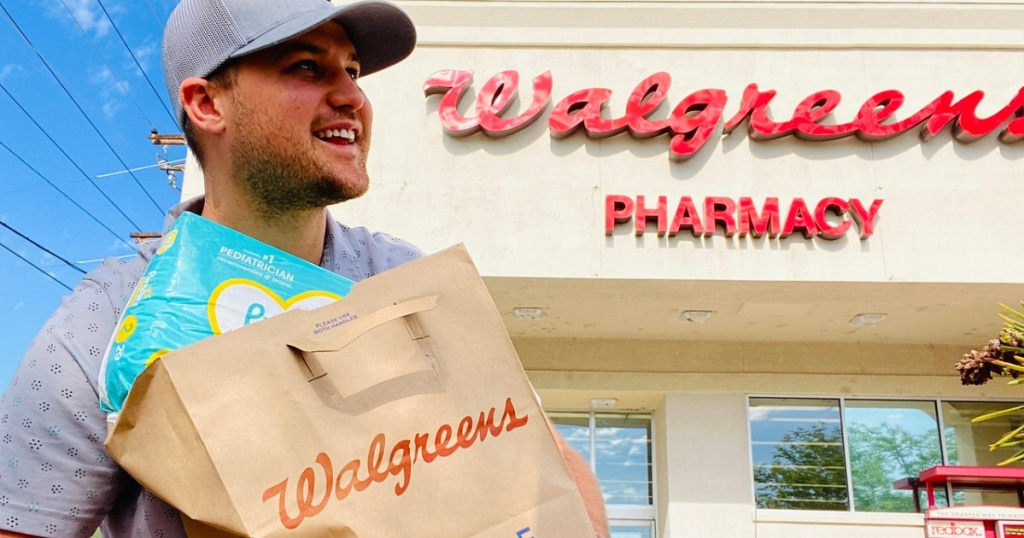 man carrying a Walgreens bag in front of a Walgreens store