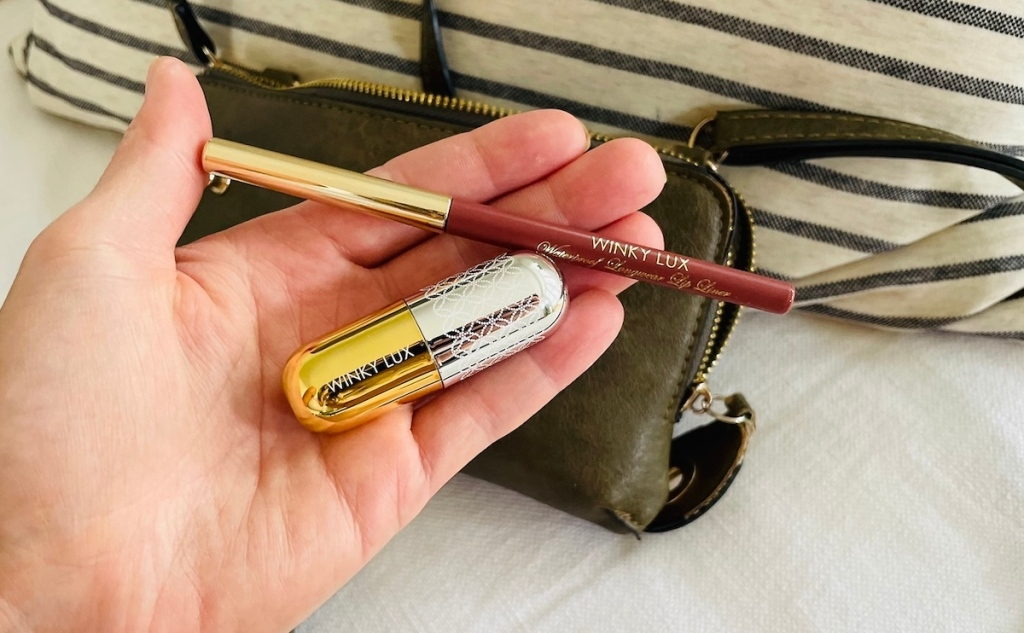 hand holding lip liner and lipstick in front of open purse