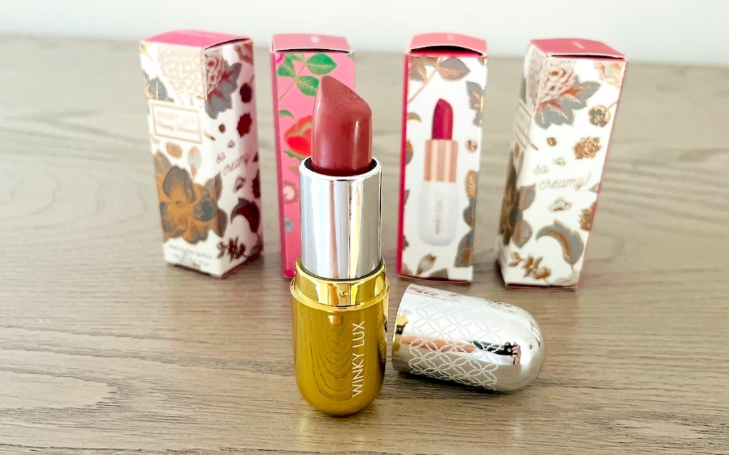 open lipstick container on wood surface with lipstick boxes in background