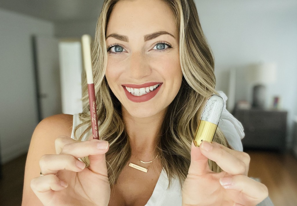 woman holding up winky lux lipstick and lip liner