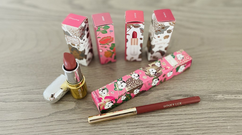 lipsticks and lipliner in winky lux boxes sitting on gray wood dresser