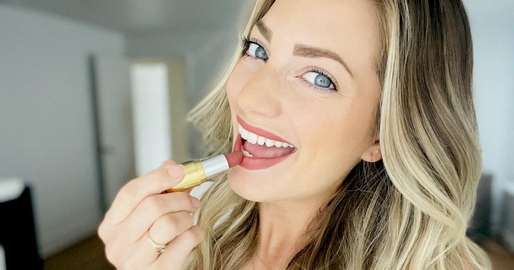 woman putting on dark pink lipstick