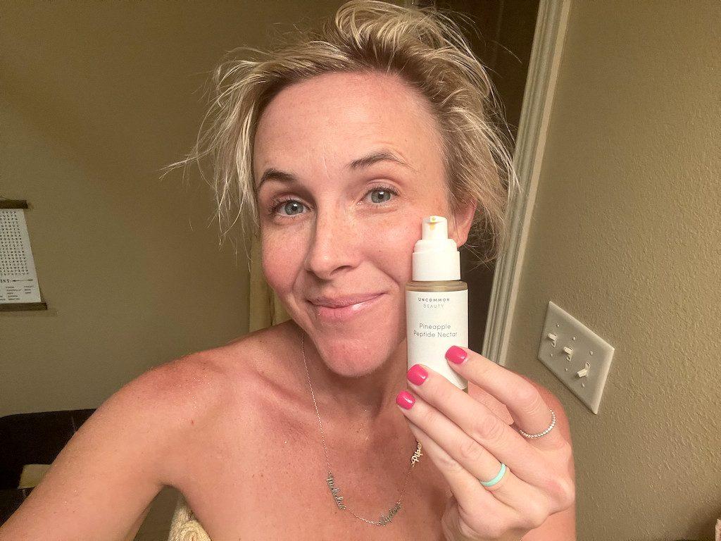 woman holding uncommon beauty vitamin c serum