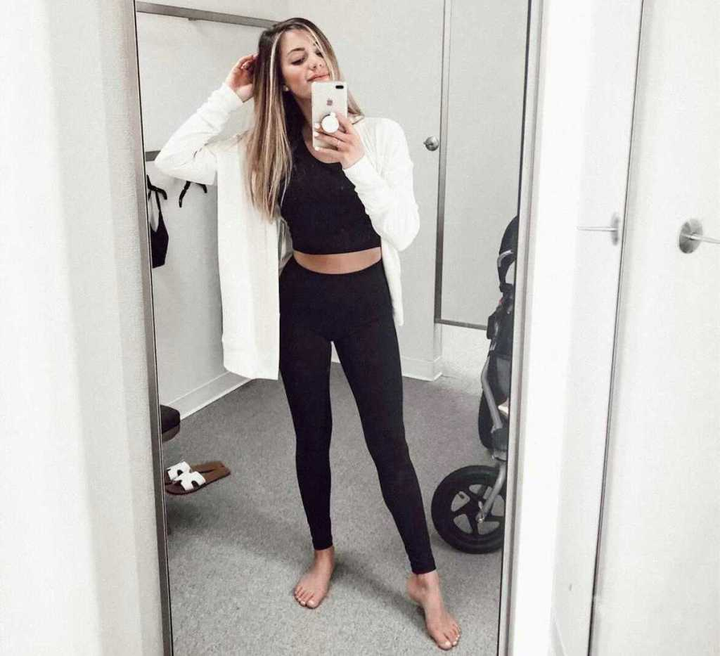 woman wearing workout clothes in nordstrom anniversary sale dressing room holding phone