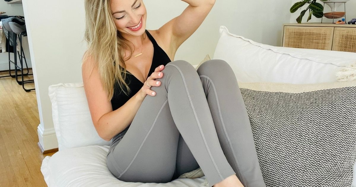 woman laying on couch in black tank and gray leggings