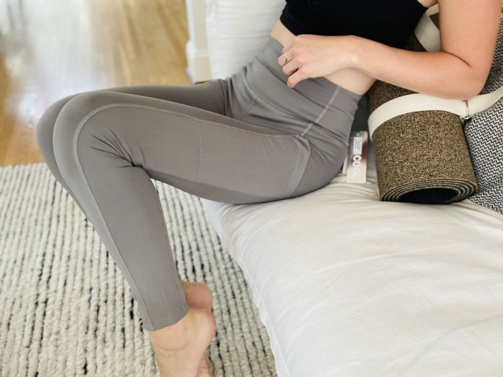 woman sitting on couch in gray leggings