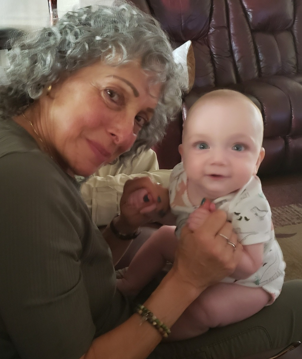 woman with baby on lap sitting on couch looking at camera
