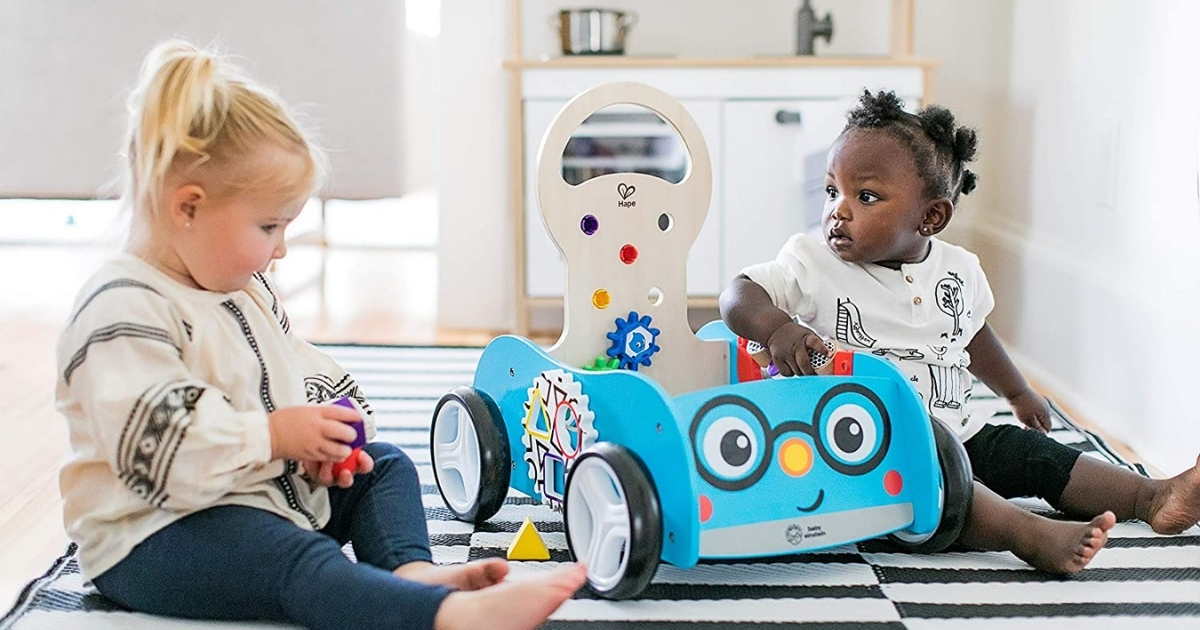 2 young girls playing with baby einstein discovery buggy