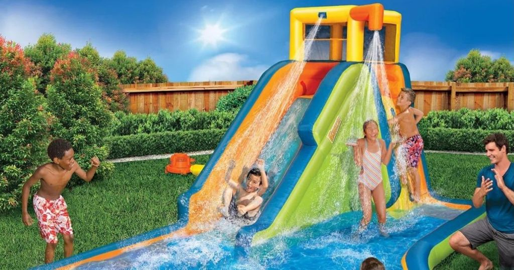 kids playing on an inflatable water slide