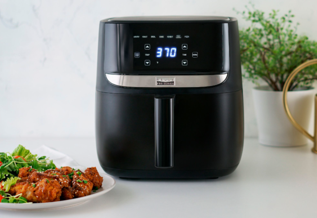 air fryer with a plate of food next to it