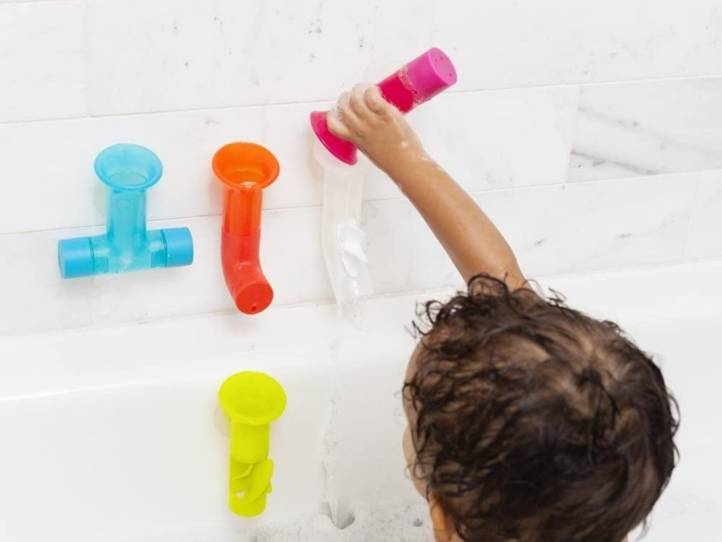 child playing with bathtub pipes