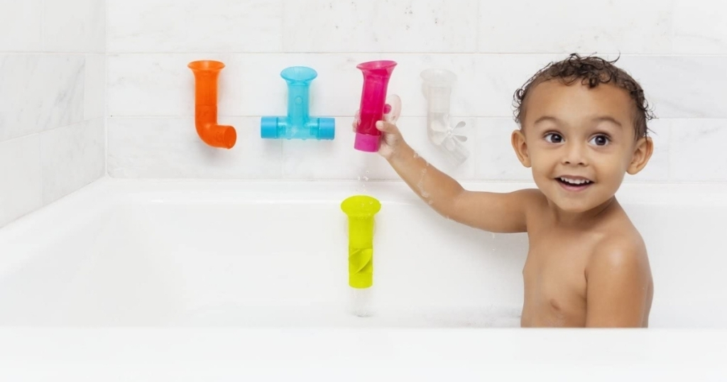 baby playing with plastic pipe set for bathtub