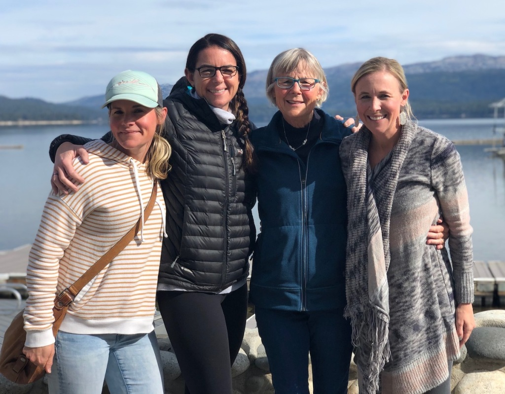 four woman standing together smiling in front of lake