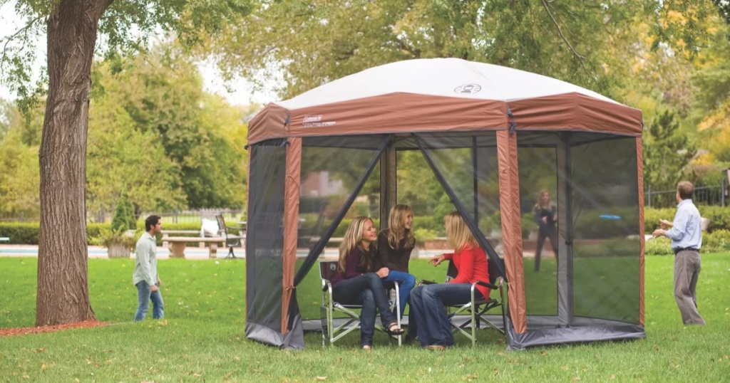 brown screened tent set up in yard with people