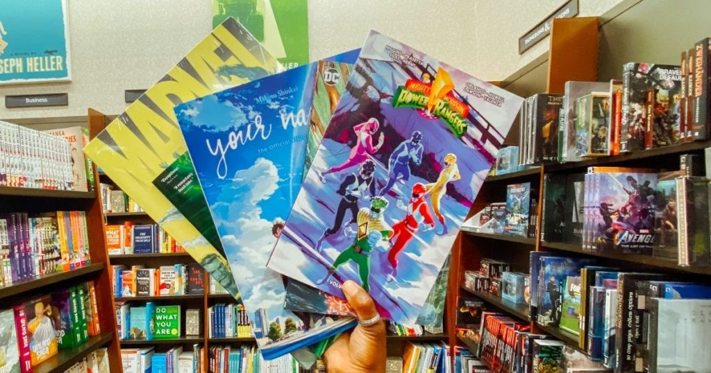 hand holding a group of comics