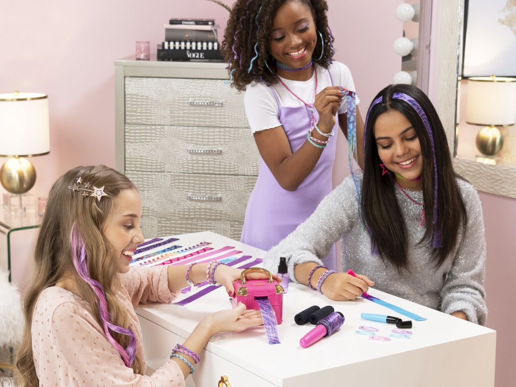three girls making colorful hair extensions