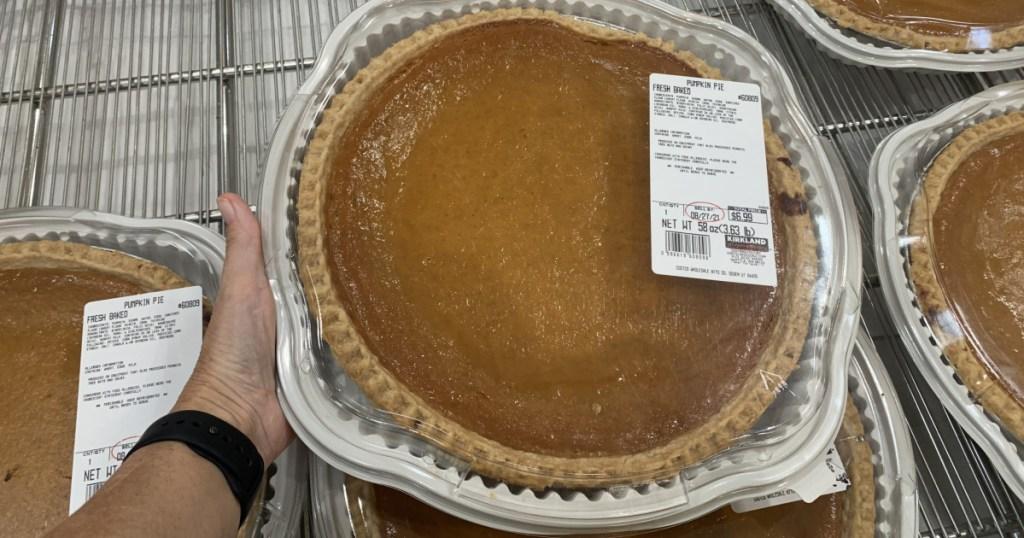 extra large pumpkin pie in hand near shopping cart