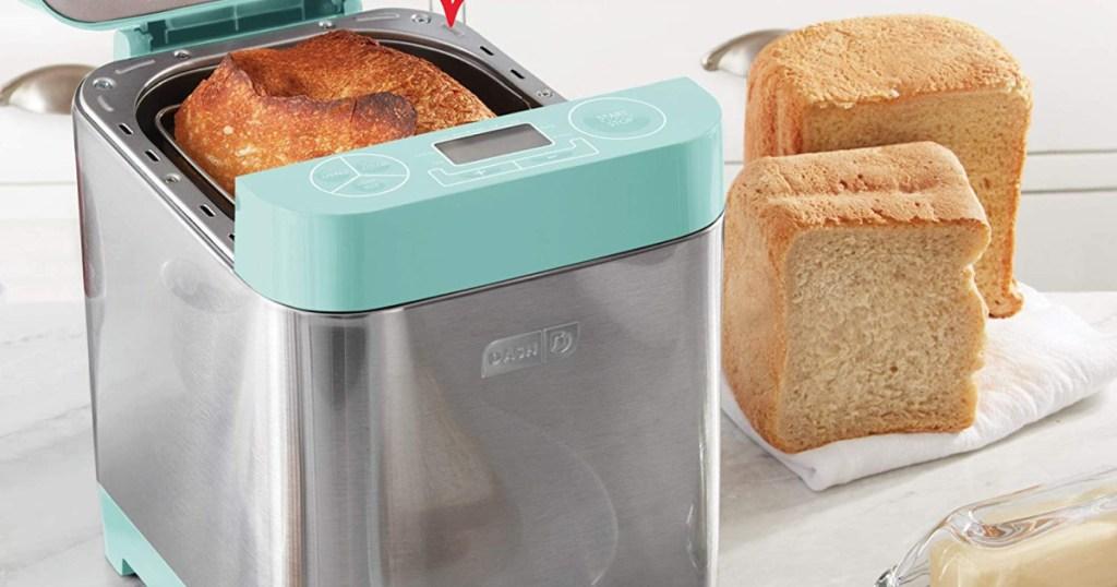 Aqua colored bread maker on counter near bread