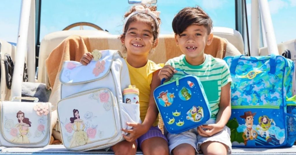 two kids holding backpacks and lunch boxes