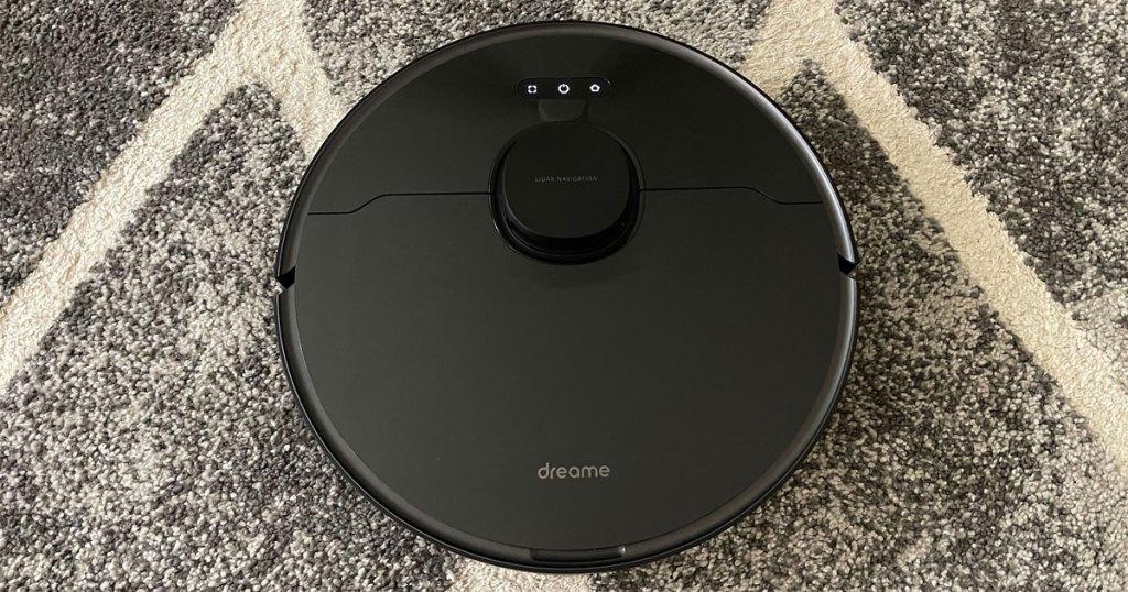 black robotic vacuum on rug