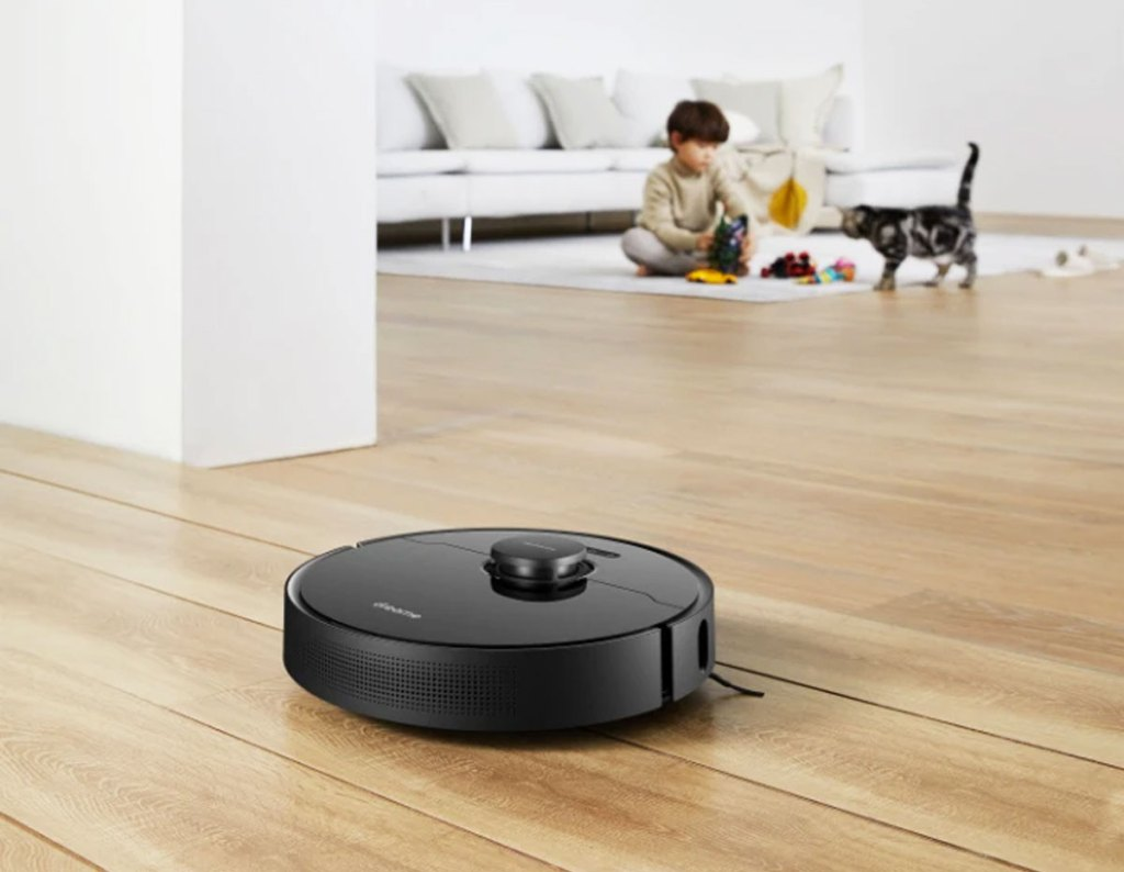 black vacuum on wood floor with cat and boy in background