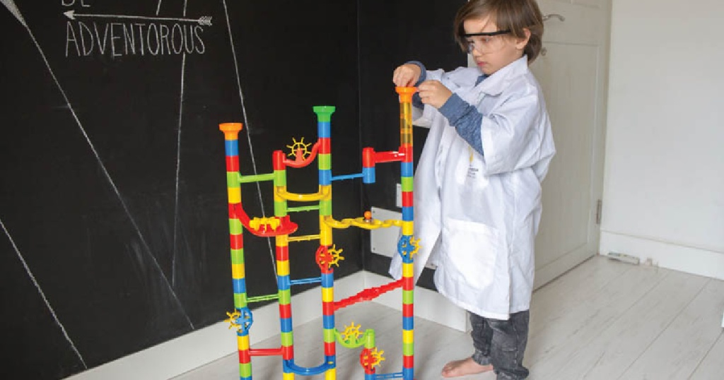 young boy playing with a marble run set