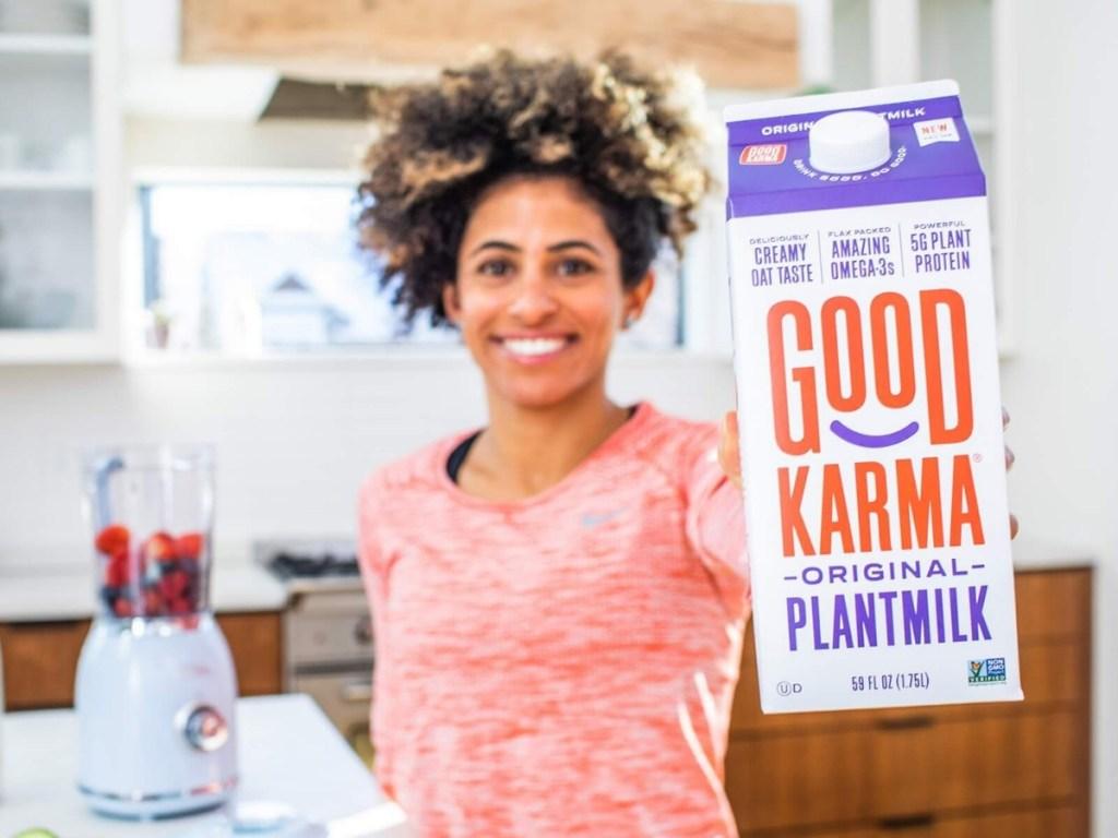 woman holding carton of good karma plantmilk original