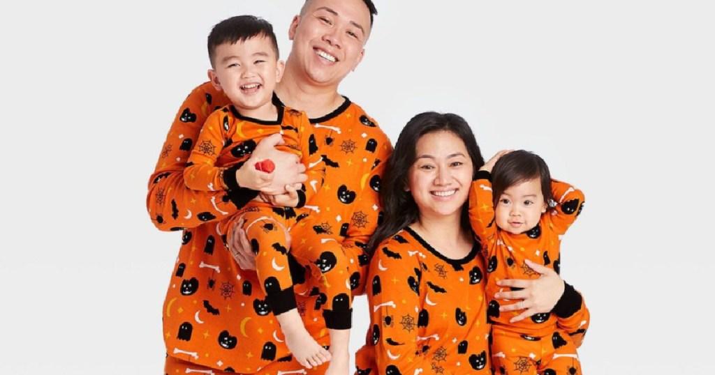 man woman and two kids wearing matching orange halloween PJs