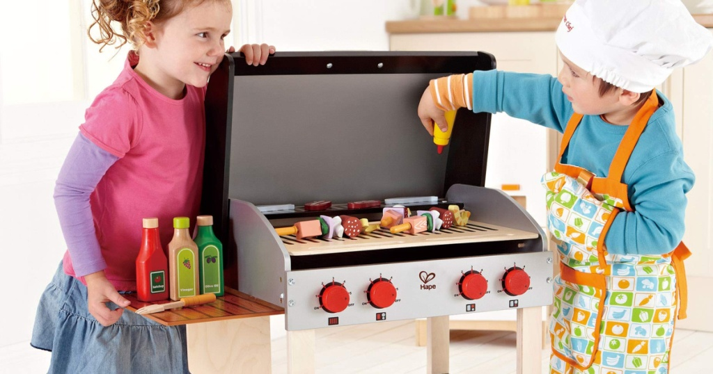 2 children standing next to a wooden hape grill