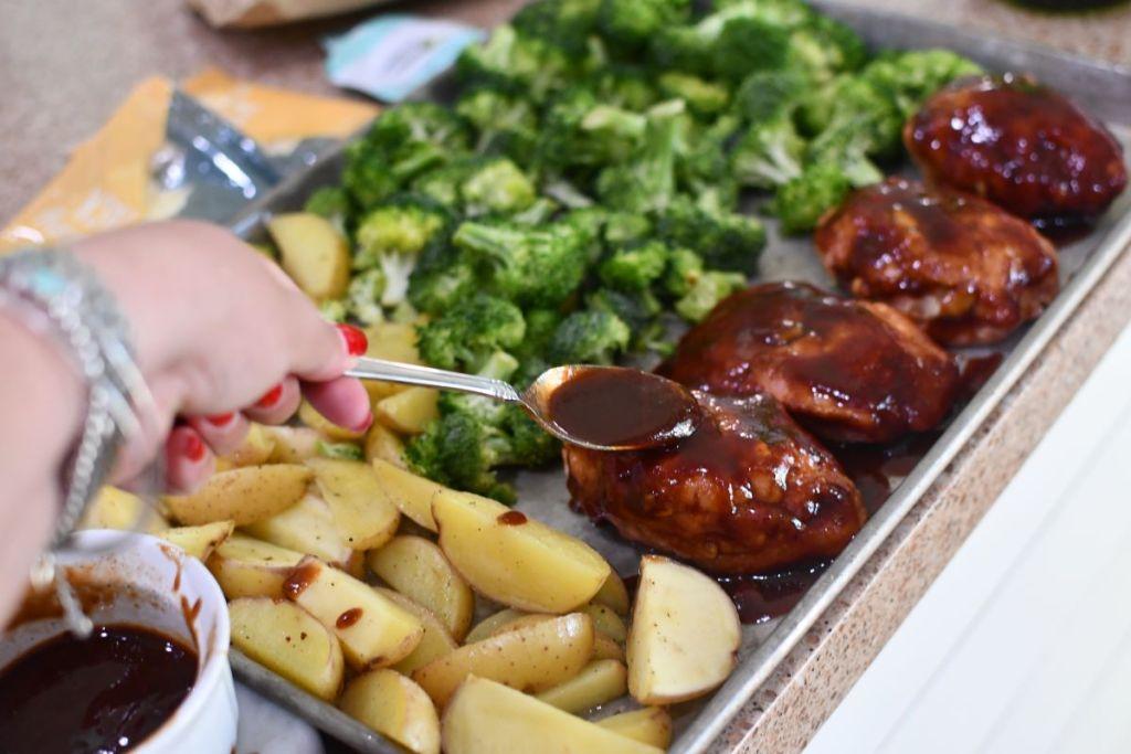 hand putting sauce on a sheet pan meal
