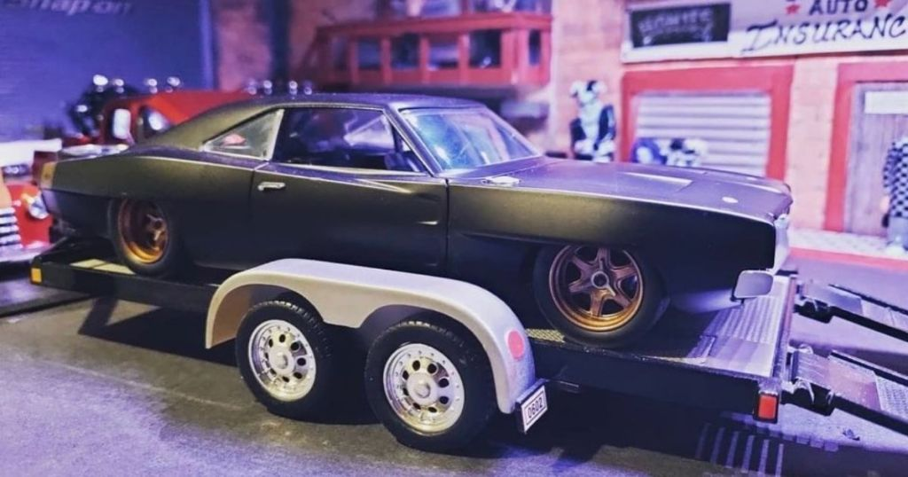 black Charger toy car on a toy trailer