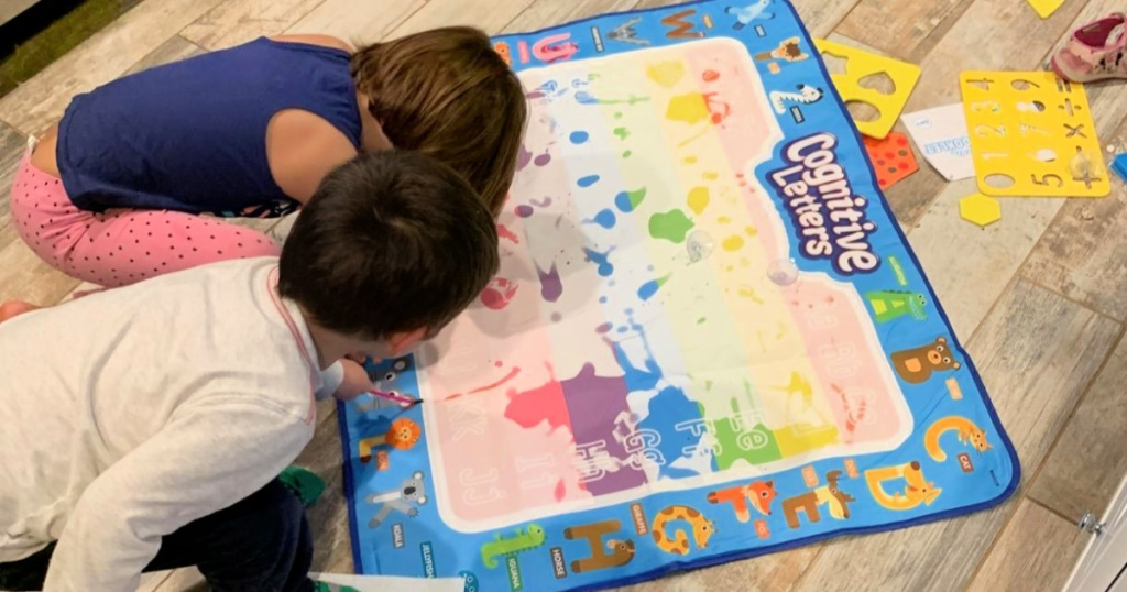 kids playing with a water doodle mat on the floor