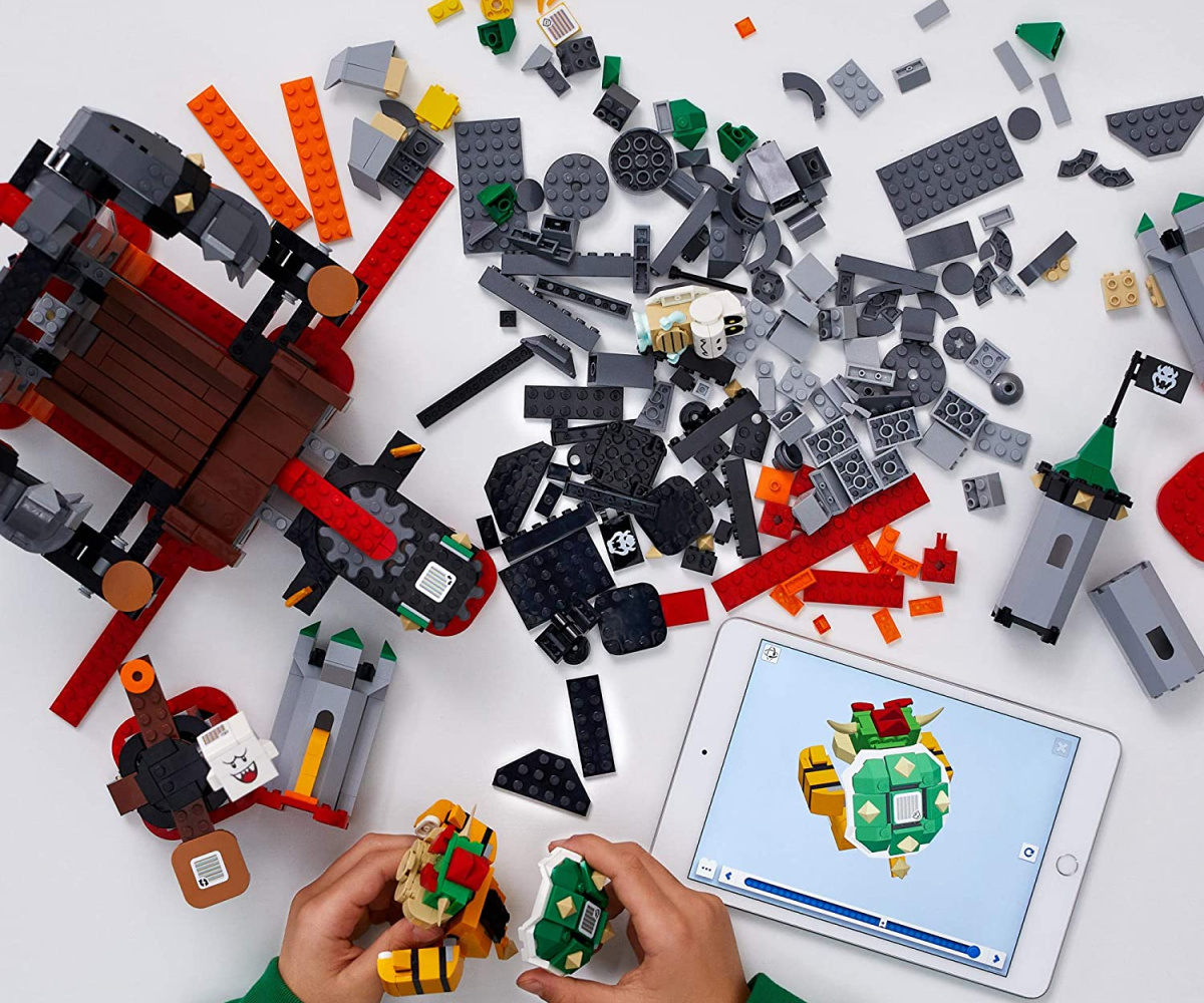 kids hands building Bowser themed LEGO set with digital directions