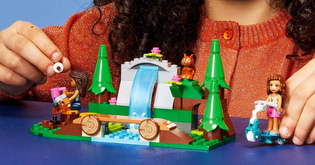 girl playing with lego waterfall set